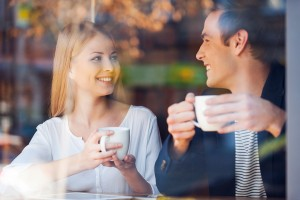 Through a glass shot of beautiful young couple looking at each other and smiling while enjoying coffee in cafe together
