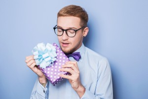Closeup portrait of happy excited young man with colorful gift b