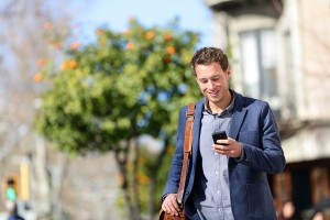 Young urban professional man using smart phone. Businessman hold